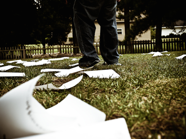 Image of papers strewn about on a lawn
