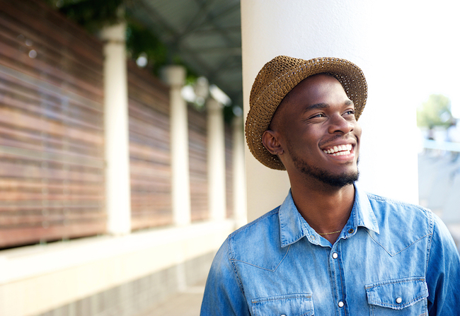 smiling man wearing a hat and denim shirt